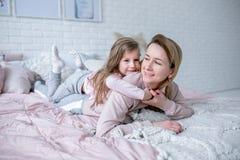A mãe nova bonita e sua filha pequena estão encontrando-se junto na cama no quarto, estão jogando-se, estão abraçando-se e estão  fotos de stock royalty free