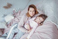 A mãe nova bonita e sua filha pequena estão encontrando-se junto na cama no quarto, estão jogando-se, estão abraçando-se e estão  fotografia de stock