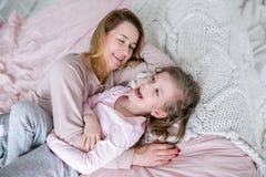 A mãe nova bonita e sua filha pequena estão encontrando-se junto na cama no quarto, estão rindo-se, estão abraçando-se e estão te imagem de stock royalty free