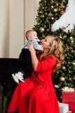 Mãe nova bonita feliz e seu bebê de um ano pequeno que sentam-se na poltrona Foto de Stock
