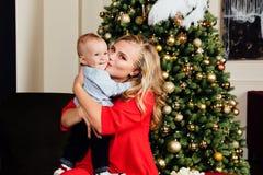 Mãe nova bonita feliz e seu bebê de um ano pequeno que sentam-se na poltrona Imagens de Stock Royalty Free