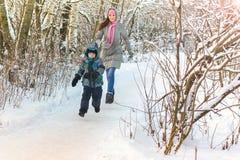 Mãe nova bonita que anda com seu filho na atualização do jogo da floresta do inverno imagem de stock royalty free