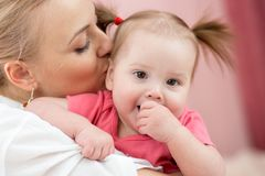 Mãe nova bonita que beija o bebê adorável fotos de stock royalty free