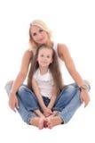 Mãe nova bonita que senta-se com a filha pequena isolada sobre imagens de stock royalty free