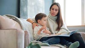 A mãe nova bonita que senta-se no sofá em sua casa a sala de visitas lê o filho uma história na orelha e aprende-o ler filme