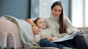 A mãe nova bonita que senta-se no sofá em sua casa a sala de visitas lê o filho uma história na orelha e aprende-o ler video estoque