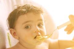 Mãe nova com a colher e o papa de aveia que alimentam s pequeno bonito doce Fotos de Stock Royalty Free