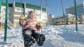 Mãe nova com a criança que balança em exterior ajustado do balanço no parque do inverno Neve que cai, queda de neve, tempo de inv