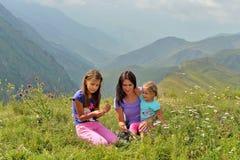 A mãe nova com duas filhas relaxa na natureza nas montanhas fotografia de stock