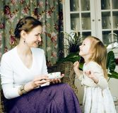 Mãe nova com a filha no vintage interior home luxuoso imagem de stock