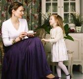 Mãe nova com a filha no vintage interior home luxuoso fotografia de stock