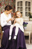 Mãe nova com a filha no vintage interior home luxuoso Foto de Stock