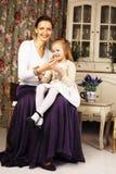 Mãe nova com a filha no vintage interior home luxuoso Imagens de Stock