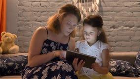 Mãe nova com filha pequena e datilografia na tabuleta e assento no sofá na casa moderna, conceito de família dentro filme