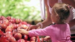 Mãe nova com a filha pequena no trole que seleciona frutos no supermercado video estoque