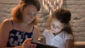 Mãe nova com a filha pequena que guarda a tabuleta e que senta-se no sofá na casa moderna, conceito de família, fora video estoque