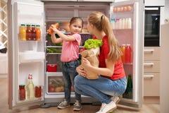 Mãe nova com a filha que põe o alimento no refrigerador foto de stock