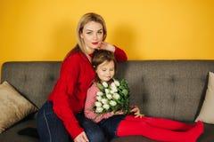 Mãe nova com o doughter que senta-se no sofá cinzento Fundo amarelo no estúdio Flores 8as do março fotografia de stock