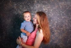 Mãe nova com seu filho pequeno nos braços felizes junto fotografia de stock royalty free