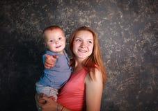 Mãe nova com seu filho pequeno nos braços felizes junto imagens de stock royalty free