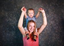 Mãe nova com seu filho pequeno nos braços felizes junto fotos de stock royalty free