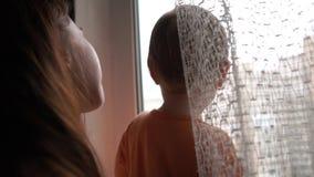 Mãe nova com seus suportes da criança perto da janela e para beijá-lo no movimento lento video estoque