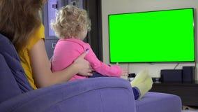 A mãe nova com sua menina da filha relaxa na tevê do sofá e do relógio Tela verde vídeos de arquivo