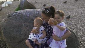 Mãe nova com suas filhas do bebê que sorriem e que olham a câmera em um rio que veste o vestido pontilhado - valores familiares filme