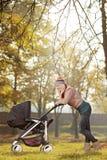 Mãe nova com um transporte de bebê que anda em um parque Imagens de Stock