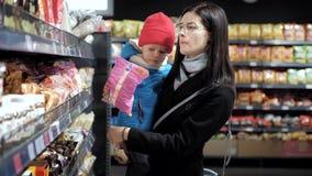 Mãe nova com uma criança dentro do supermercado que escolhe bens vídeos de arquivo