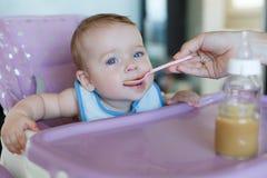 A mãe nova dá de comer de colher a criança Imagem de Stock