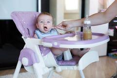 A mãe nova dá de comer de colher a criança Fotos de Stock Royalty Free