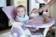 A mãe nova dá de comer de colher a criança Fotografia de Stock Royalty Free