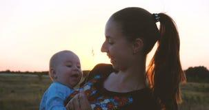 Mãe nova de sorriso e sua criança que apreciam a vida em um campo no por do sol no slo-mo filme