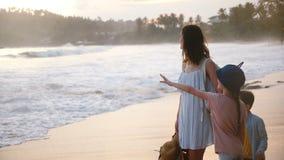 Mãe nova de sorriso feliz junto com duas crianças pequenas que falam na praia tropical exótica do mar no por do sol bonito vídeos de arquivo