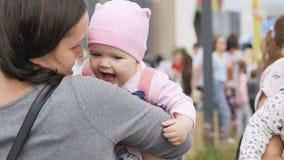 A mãe nova do close up mantém o bebê bonito na alameda contra povos vídeos de arquivo