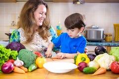 A mãe nova do cozinheiro que está com seu filho pequeno no kitche Fotos de Stock Royalty Free