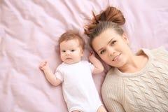 Mãe nova e bebê bonito na cama fotos de stock