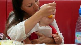 Mãe nova e bebê bonito que sentam-se em um café O Mum alimenta com uma criança do menino da colher que come o puré do fruto video estoque