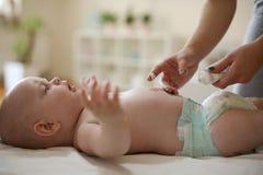 Mãe nova e bebê despido, cuidados com a pele Fim acima fotos de stock royalty free