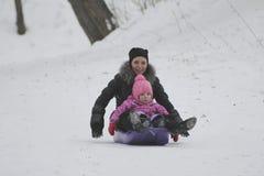 A mãe nova e a equitação bonito da filha no pequeno trenó no inverno estacionam fotografia de stock