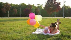 A mãe nova e a filha infantil bonito na roupa cor-de-rosa encontram-se na cobertura branca colocada na grama verde no parque pict video estoque