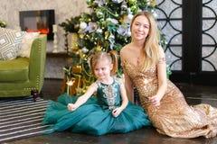 Mãe nova e filha pequena com a luz de bengal que senta-se no assoalho perto da árvore de Natal fotografia de stock royalty free