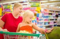 A mãe nova e a menina adorável no carrinho de compras olham j gigante Imagem de Stock