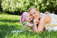 A mãe e o bebê novos snuggle seus mordentes, sentando-se na grama fotos de stock royalty free