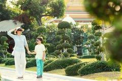 Mãe nova e seu filho pequeno que andam em jardins verdes das árvores dos bonsais em Wat Arun Imagens de Stock