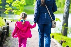 Mãe nova e sua filha pequena que andam perto da lagoa no parque imagens de stock royalty free