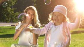 A mãe nova e sua filha que jogam com bolhas de sabão na cidade estacionam Movimento lento vídeos de arquivo