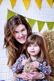 Mãe nova e sua filha que sorriem e que guardam um coelho fotografia de stock