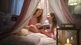 Mãe nova e sua filha que têm o divertimento usando a tabuleta que joga apps filme